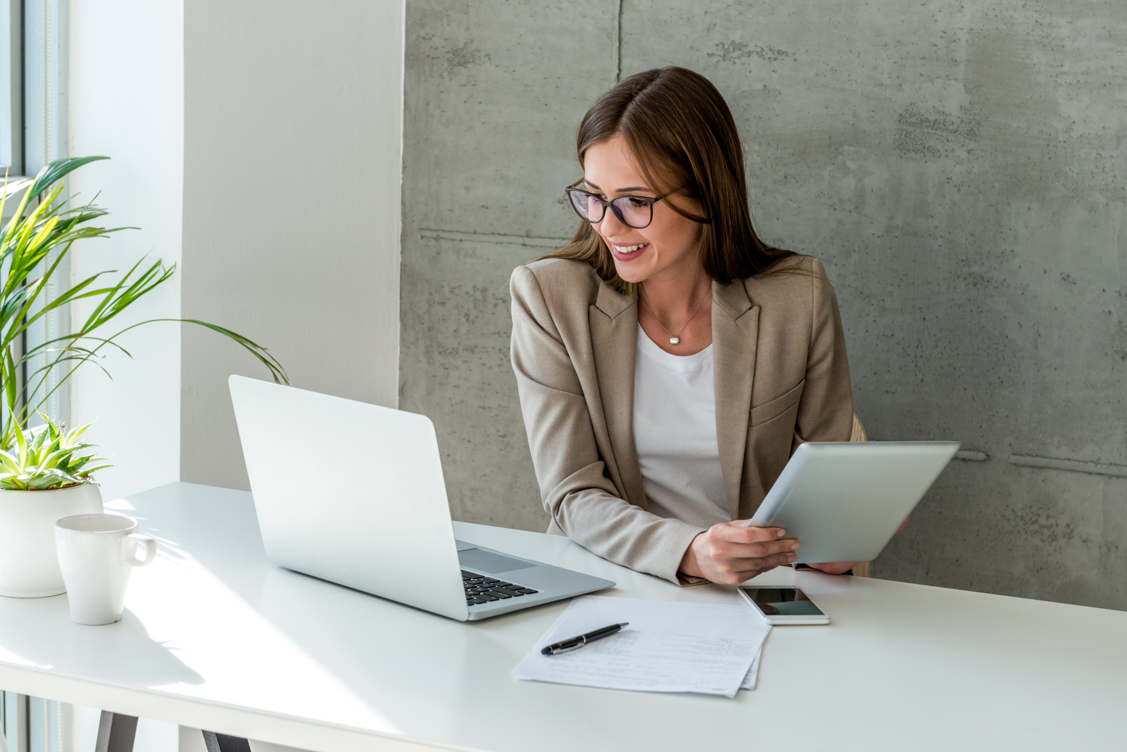 Woman looking at report on laptop